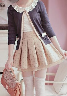 A very cute outfit with the blue cardigan with pink detailing with the pleated pink skirt. Along with the pastel detailed purse and the white tights.