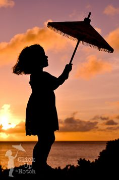 Under the Umbrellas & Parasols is an adorable young girl holding a parasol with a background of the sunset