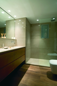 A luxurious and modern bachelors' master bathroom in the center of the city. American walnut wood parquet by Mafi and Ligouriou marble in a custom made shower. the mixers are from Dornbracht. Created by V&V Interiors
