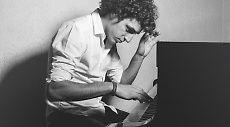Benjamin sitting at his piano playing music.