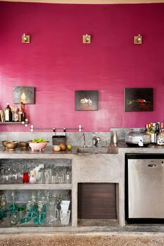 Modern kitchen with stainless steel appliances, concrete open cabinets and bench and bright pink walls!