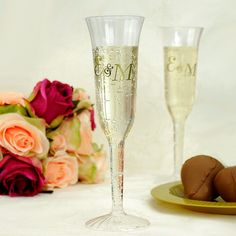 Personalized clear plastic champagne flutes printed in gold imprint color with monogram M-36 and splendid lettering style
