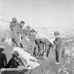 """The Korean War, December 1952 - Company Sergeant Major Harry McDortch (without headgear), """"A"""" Company, 1st Battalion, The King's Liverpool Regiment, pays a routine visit to one of the forward platoons of his company serving at the front in Korea. The men in this photograph are digging in a new bunker, a job which helped to keep them warm in the cold Korean winter."""