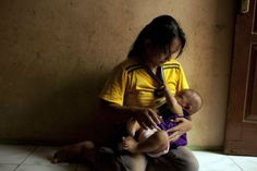@WHO #HealthEquity #toolkit #LeaveNobodyBehind A woman breastfeeds her baby in a dark room in Jakarta, Indonesia #COMD5000 #COMD5001