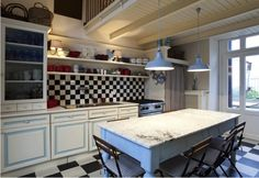 The checkerboard floor and backsplash of this galley kitchen call for Spare White (SW 6203) walls.
