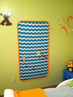 Kids magnet board! Lg oil drip pan from Wal-Mart, covered in fabric, trimmed with duct tape!!