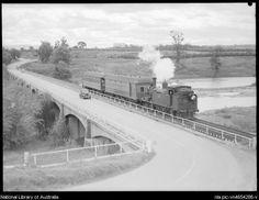 Car and steam train crossing Richmond Bridge. 1945
