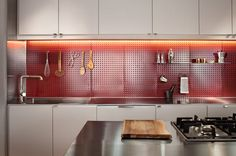 Kitchen with Ikea cabinets and red pegboard backsplash, with accent lighting.