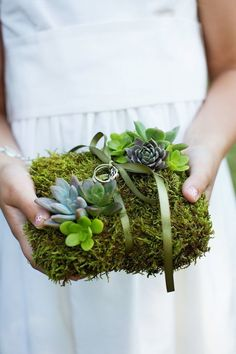 Succulents have been used in wedding bouquets, centerpieces, as favors, and even as motifs for invitations. However, this trendy plant is given another role in this unique ring bearer pillow covered entirely in moss and these little cuties. | 11 Fun Ring Bearer Boxes, Pillows, and More