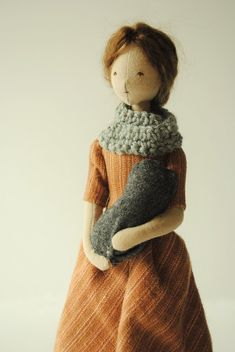 2 of 4 A small cloth doll with bundled baby, designed and handmade in Australia by Margeaux Davis. Made from cotton remnants, she wears a hand-stitched, brown cotton dress and is cradling a baby wrapped in a woollen blanket. She also wears a grey cowl and grey linen hooded cloak with hand embroidered trim. This is a completely one of a kind, unique doll, handmade from carefully salvaged fabric remnants and worn-out antique clothing. She will have some visible stitching and slight imper...