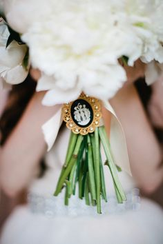 Lush white peony bouquet with white ribbon and black and white cameo brooch. Photo: Pam Cooley