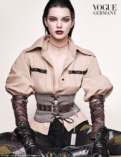 How low can it go:For another shot, the supermodel donned an open camel coloured shirt with blouson sleeves tucked into leather arm warmers