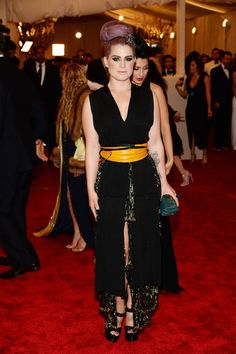 Kelly Osbourne Evening Dress - Kelly chose a classic black dress with some unique touches such as the shimmery green underlay, and a mustard yellow belt for her look at the 2013 Met Gala.