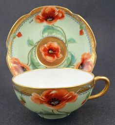 $225 This porcelain tea cup and saucer was produced by Haviland Limoges and decorated in the USA by the Stouffer Studio around 1900. The set is beautifully hand painted and artist signed. The design is representative of the art nouveau period. Large flowing poppies stretch across the porcelain. The ground color is a pleasant mint green. There are black painted accents on the heavy gilding. This is a vibrant and exciting cup and saucer.