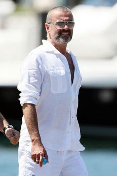 George Michael Photos Photos - Singer George Michael looks to have packed on a few extra pounds on his Australian vacation but appears totally unfazed by it. George and his partner Fadi Fawaz, lunched at the Botanic Garden before enjoying the sights of Sydney while having a cigarette. - George Michael Vacations in Australia