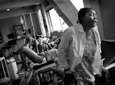 .A woman experiencing post delivery pain moments after delivering her baby lifts herself off the table to head outside for recovery, so another woman can lay down and give birth at a clinic just outside Port-au-Prince