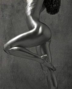 """Publié notamment par Marie Claire, Vogue ou encore Playboy, Guido Argentini est un photographe italien basé aux États-Unis. Dans un projet qu'il a nommé """"Silver"""", il tente de montrer dans son œuvre toute l'élégance des femmes à travers la mise en scène de corps sans aucune vulgarité. On y voit des femmes nues et recouvertes de peintures argentées."""
