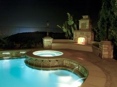 Night swimming just got a lot better. This elegant poolside retreat features an outdoor fireplace with bench seating and a heated swimming pool with an elevated hot tub and plenty of soothing water features. Plus, the fireplace is close enough to the pool Outdoor Rooms, Outdoor Living, Outdoor Showers, Outdoor Kitchens, Outdoor Stuff, Outdoor Fireplace Designs, Outdoor Fireplaces, Outside Fireplace, Backyard Fireplace