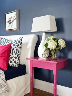 Pink bedside table. Navy wall. White bedspread.