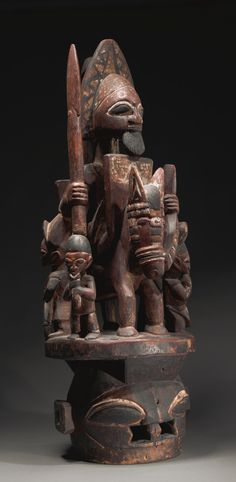 A FINE YORUBA EPA HELMET MASK, POSSIBLY BY BAMGBOYE OF ODO OWO (CA. 1895-1978), NIGERIA  the janiform helmet pierced at the mouth with large hemispherical eyes and square ears, supporting an elaborate superstructure of the warrior king riding a horse, holding a spear in his right hand and the reigns in his left, his bearded face surmounted by a tall crested hat with a pendant flange at the reverse touching the high backed saddle, and surrounded at the base by four diminuative musicians;