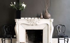 An ornate vintage fireplace against a grey wall is stunning