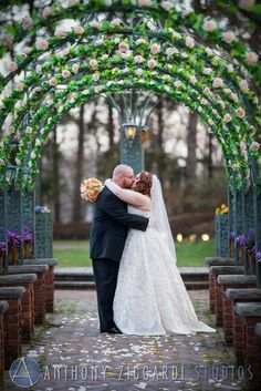 Beautiful shot of the happy newlyweds under a floral archway.  #spring #flowers #justmarried #happycouple #kiss #love #anthonyziccardistudios #aziccardi