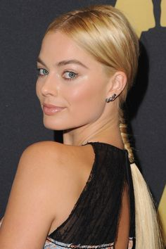 Rather than finishing off her sleek middle-parted 'do with a low chignon or ponytail, Robbie went for a whimsical French braid.   - ELLE.com