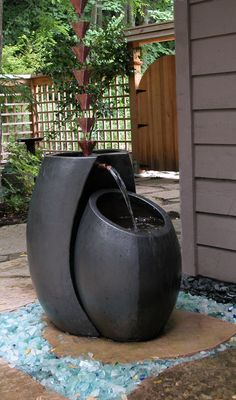 What a creative way of using a rain chain. Love the fountain and the glass surrounding it. Design by Phyllis Warman.
