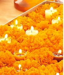 I like the way candles are nestled amongst the marigolds. This could be used in low flower arrangements - candles or votives are nestled into the arrangement.