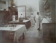 Dining with Edward VII at Polesden Lacey: Chef Delachaume and his ladies in the kitchen c.1905. Note the large brand new central range. The nearest table, which is neatly covered with cloth is dressed with the chef's seasoning boxes.