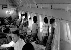 "Orphans aboard the first ""Operation Babylift"" flight at the end of the Vietnam War look through the windows of World Airways DC-8 jet as it flies them to the United States in April 1975."