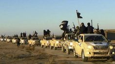 FILE - In this undated file photo released by a militant website, which has been verified and is consistent with other AP reporting, militants of the Islamic State group hold up their weapons and wave flags on their vehicles in a convoy on a road leading leading to Iraq, while riding in Raqqa, Syria.