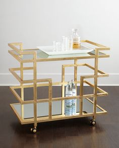 "Handcrafted linear bar cart. Iron frame with hand-painted gold-leaf finish. Three mirrored shelves. 36""W x 22""D x 32""T. Imported. Boxed weight, approximately 75 lbs."