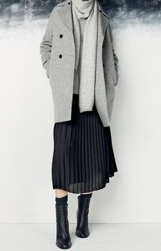 a simple, modern winter outfit with a gray coat, black pleated skirt and ankle boots