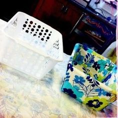 Create a pretty storage bin by covering a dollar store plastic basket with fabric.  Use hot glue to attach the fabric (no sewing needed). by lydia