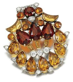 CITRINE AND DIAMOND DRESS CLIP, CARTIER, 1940S.  Of palmette design set with mixed-cut citrines accented with brilliant-cut diamonds, signed Cartier London.