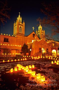 At the Old Town plaza in Albuquerque, New Mexico, the San Felipe de Neri church is decorated with hundreds of faralitos, sometimes called lunimarias, during the celebration on Christmas Eve. Charles Mann Photography