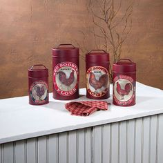 Set of 4 safety coated, food approved metal canisters finished in a dark red, colorful vintage branded label rooster motif with tight fitting lids, for for