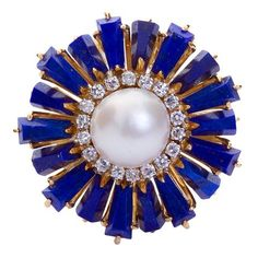A retro lapis lazuli burst and 9 mm pearl center with diamond accents in 18 karat yellow gold ring. Ring size 6-7 (adjustable). No. 4190