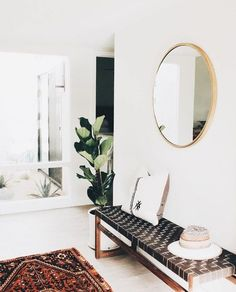 This circular mirror is the perfect addition to this white wall.