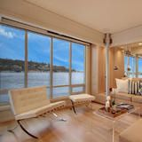 The lower level hosts an open floor plan and floor-to-ceiling windows. Sliding doors lead to the deck, just fingertips away from the glittering water.