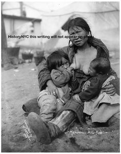 This photograph an Inuit Eskimo woman breastfeeding her baby. The photograph was taken in 1904 by Frank H. Nowell.