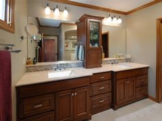 A center wall cabinet and recessed drawer stack break up a long line of vanity cabinets.
