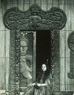 Guide Maggie in a korowai, seated in carved doorway of 'Rauru'. Photograph from the collection of the Rotorua Museum.