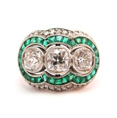 Vintage three stone diamond engagement ring with lovely emerald surround.