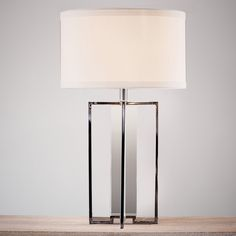 A most elegant lamp with a solid crystal central column and stainless steel upright sections on the outside. Classic white linen shade. A timeless showstopper.