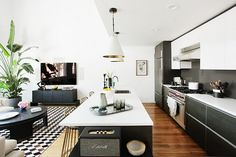 Modern, monochrome kitchen with black wood cabinents, a white island, wood floors, and white and gold pendant lights