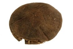Photograph: Man's dark brown, woollen, knitted cap. Silk ribbons can be seen, sewn to the brim. ca earl 1500s. knitted in the round in stocking stitch. Short lengths of plain-weave silk ribbon have been inserted in pairs into the back and sides of the cap, which extend down the neck. Museum of London.