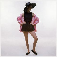 Model wearing a black Givenchy linen romper with a bow at the waist, worn with a pink and white organza jacket and a black straw hat 1969 Photo Bert Stern