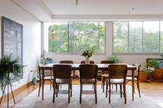 Sala de jantar iluminada tem mesa e cadeiras de madeira além de muitas plantas.